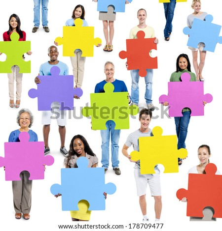 Diverse World People Holding Colorful Jigsaw Pieces - stock photo