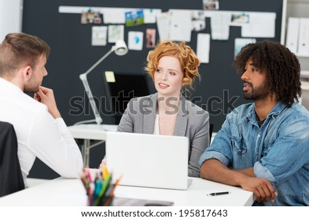Diverse young businesspeople with a young man, beautiful woman and modern African American sitting at a desk around a computer having a discussion - stock photo