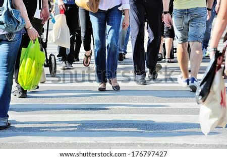 Diversified crowd crossing street - stock photo