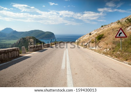 Dividing line and right turn sign on the coastal mountain highway in Montenegro - stock photo