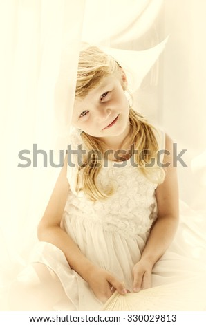 divine blond girl sitting by the curtain desaturated portrait - stock photo