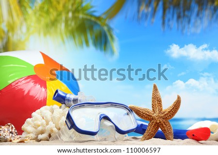 Diving goggles,snorkel and ball on sand beach - stock photo