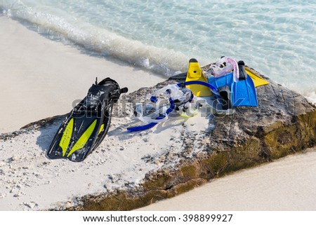 diving, snorkeling, leisure and summer vacations concept - scubas, masks and flippers on beach - stock photo