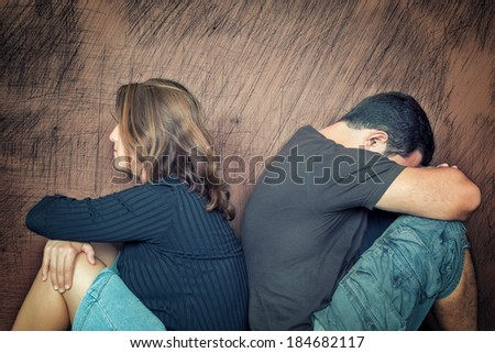 Divorce,fight,problems - Young couple angry at each other sitting back to back - stock photo