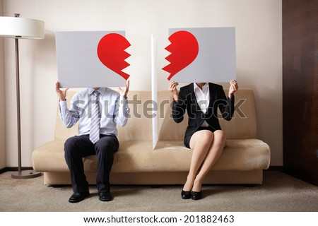 Divorce - Sad young couple holding billboard sign with break love heart, concept for divorce - stock photo