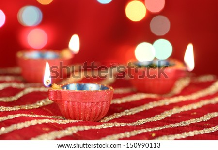 Diwali Diya with blurred festive lights in the background - stock photo