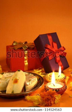 Diwali festival celebration with gifts, sweets, and  lamps - stock photo