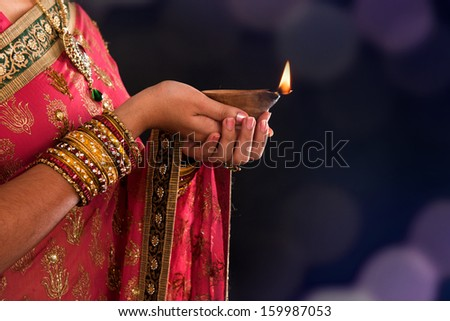 Diwali or deepavali photo with female hands holding oil lamp during festival of light - stock photo