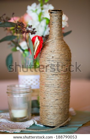 DIY wedding decor table centerpieces with wine bottles wrapped in burlap twine and rose flowers. - stock photo