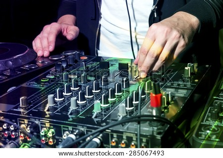 DJ at nightclub party mixes track on sound mixer, colorful laser lights, professional stereo electronic equipment, selective focus  - stock photo