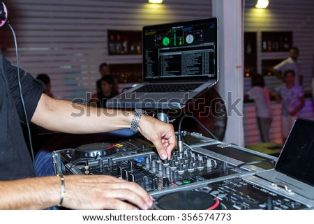 Dj hands on equipment deck and mixer with vinyl record at party . - stock photo