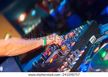 DJ hands on the remote, nightclub - stock photo