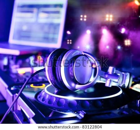 Dj mixer with headphones at a nightclub - stock photo