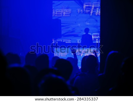 Dj mixes the track in the nightclub at party against the backdrop of a large LED screen. Silhouettes of dancing people - stock photo