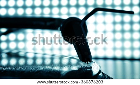 Dj needle stylus on spinning record, blur light background - stock photo