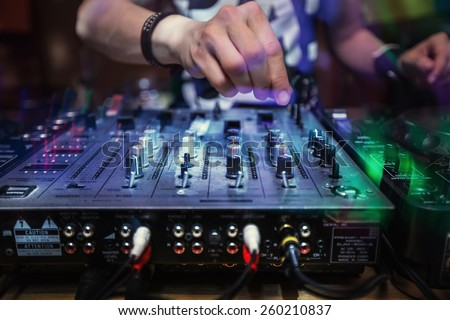 Dj playing disco house progressive electro music at the concert. DJ hands on equipment - stock photo