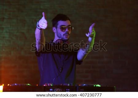 DJ playing music at mixer on blurred brick wall background - stock photo