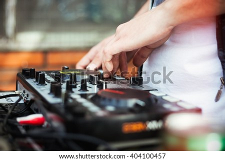 Dj playing music on modern midi controller turntable. New audio technology for mixing tracks in digital format. Shallow depth of field, unrecognizable male model.  - stock photo