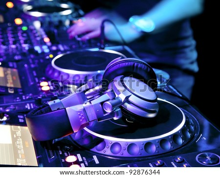 Dj playing the track in the nightclub at a party. DJ headphones - stock photo