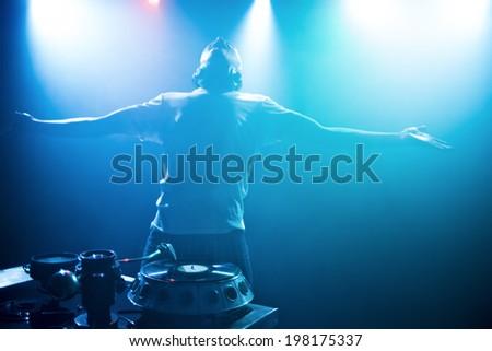 DJ raises his hands - stock photo