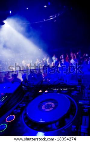 Dj?s turntable, blurred crowd on the background - stock photo