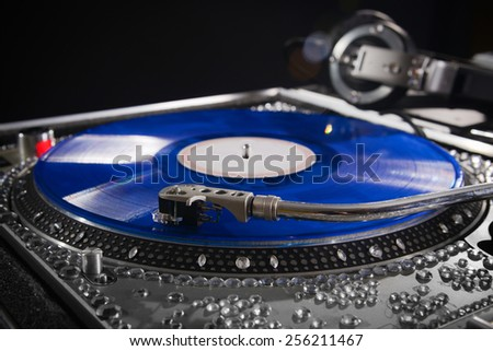 Dj turn table with blue vinyl album with headphones at nightclub - stock photo