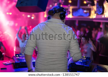DJ turns the records at the club - stock photo