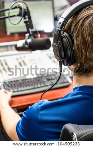 Dj working in front of a microphone on the radio, from the back - stock photo