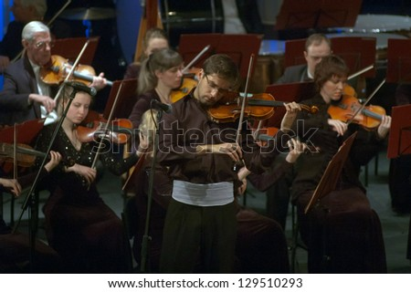DNEPROPETROVSK, UKRAINE - FEBRUARY 25: Violinist Emanuel Salvador (Portugal) and Academic Symphony Orchestra perform music of Tchaikovsky on February 25, 2013 in Dnepropetrovsk, Ukraine - stock photo