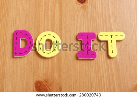 DO IT, spell by woody puzzle letters with woody background - stock photo