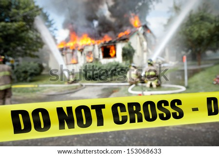 Do not cross tape with firefighters and a burning house in the background - stock photo