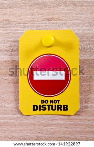 Do not disturb label with a thumbtack on a wooden background/Do not disturb label - stock photo