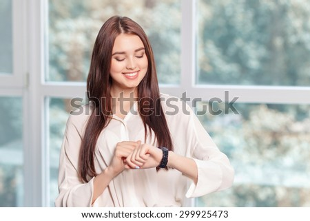Do not hurry. Upbeat positive business woman keeping glance down and looking at her wrist watch while standing near window - stock photo