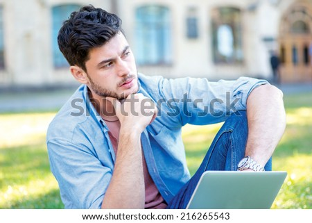 Do not put the exam. Handsome guy student holding a laptop and holding his chin while sitting on the grass near the campus of the University at the break. - stock photo