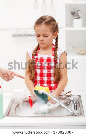 Do the dishes this instant - sad and grumpy little girl ordered to wash up tableware - stock photo