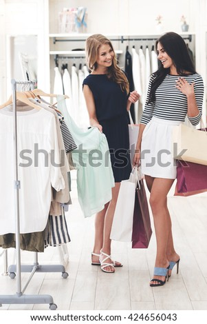 Do you like this color? Two beautiful women with shopping bags looking at each other with smile while standing hear hanger at the clothing store - stock photo