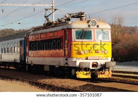 DOBRANY, CZECH REPUBLIC - DECEMBER 23, 2015: Czech Railways passenger train with Locomotive Type 242 arriving to the railway station. Czech Railways is the main railway operator in the Czech Republic. - stock photo