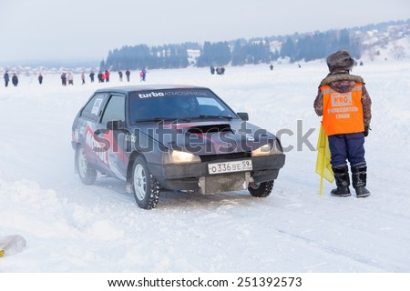 Dobryanka, Russia - February 7, 2015. Urban ice race. Black VAZ-2114 and organizer of  race on snowy highway - stock photo