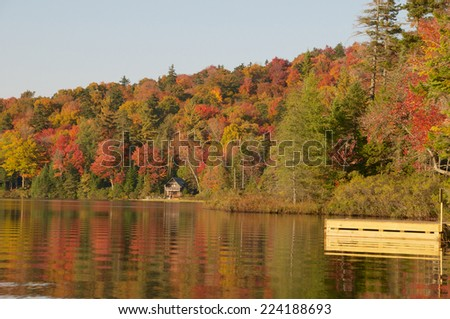 Dock lays on top of the calm still lake water on a sunny autumn day - stock photo