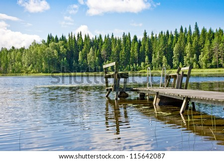Dock or pier on lake in summer day. Finland - stock photo