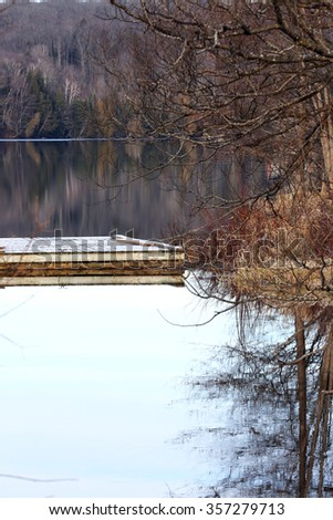 dock reflecting in icy water at treed shoreline in fall season - stock photo
