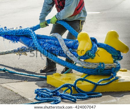 Dock worker pulls on heavy blue ropes of an ocean-going passenger ship are wrapped around a yellow mooring bollard on a city pier in the harbor. - stock photo