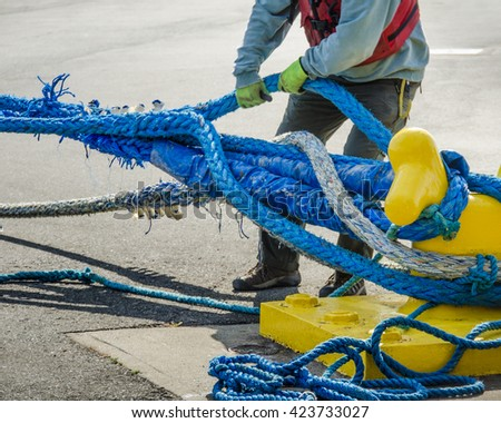 Dock worker pulls on heavy blue ropes of an ocean-going ship are wrapped around a yellow mooring bollard on a city pier in the harbor.  - stock photo
