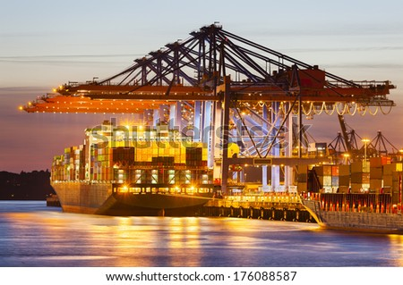 Docked container ship in harbor at dusk. - stock photo