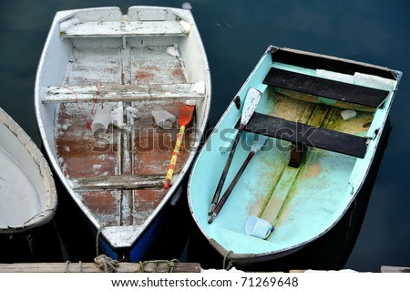 Docked Skiffs and rowboats in calm safe harbor waters - stock photo