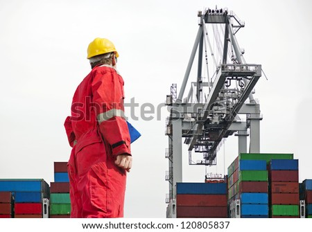 Docker overseeing a large crane, unloading containers - stock photo