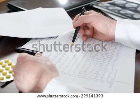 Doctor analyzing an electrocardiogram at his desk - stock photo