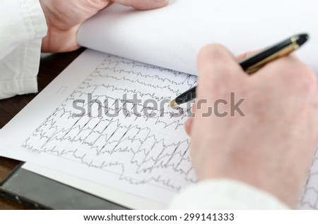 Doctor analyzing an electrocardiogram, closeup - stock photo