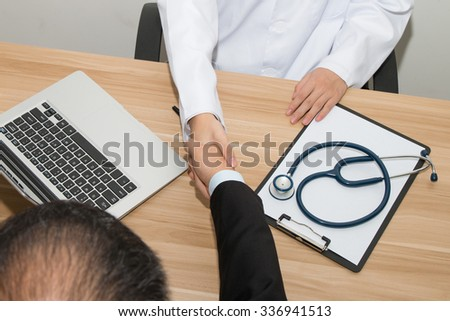 Doctor and businessman shaking hands - stock photo