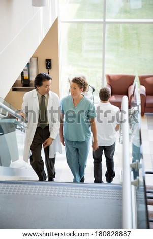 Doctor and nurse discussing while walking on stairs in hospital - stock photo